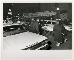 [Officers and Injured Man on Gurney in a Street]