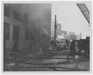 Primary view of object titled '[Firefighter's Ladders Propped Up Against Smoking Building]'.