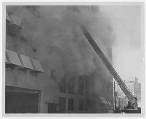 Primary view of object titled '[Firefighter's Ladder Extending Towards Smoking Building]'.