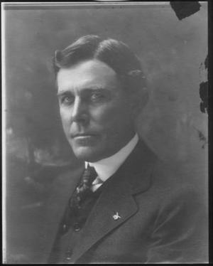 [Albert Peyton George wearing a dark colored three piece suit, white shirt, and print tie]