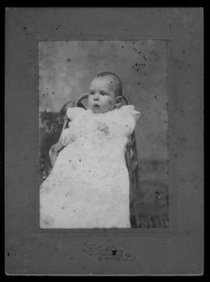 Primary view of object titled '[An infant sitting in a chair and wearing a white gown with lace insets]'.