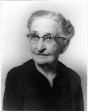[Mamie George wearing glasses and a black dress]