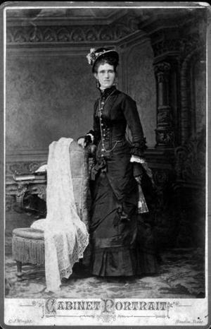 Primary view of object titled '[A woman standing beside a chair wearing a black dress and hat]'.