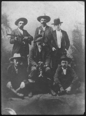 [Photograph of six men with a dog]