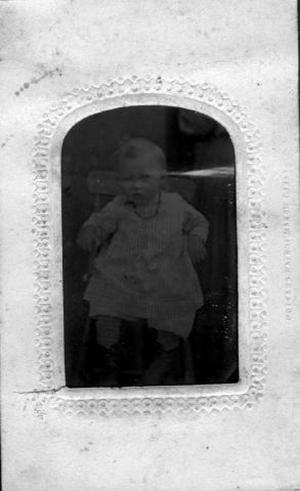 Primary view of object titled '[A young boy wearing a vertically striped gown]'.