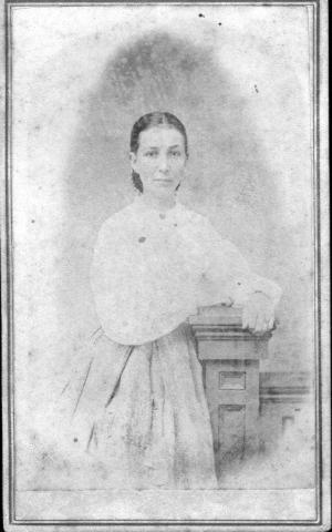 Primary view of object titled '[A young woman leaning against a waist high post]'.