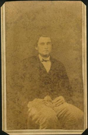Primary view of object titled '[A young man sitting in a chair with his right hand is in his pocket]'.