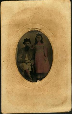 [A man sitting in a chair and a young girl with her arm resting on him]