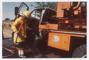 Primary view of object titled '[City of Denton fireman putting out fire on a truck]'.