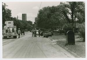 Primary view of object titled '[Utility crews trying to remove telephone pole from vehicle]'.