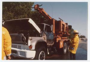 Primary view of object titled '[Two City of Denton firemen assessing fire damage to truck]'.