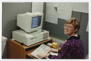 Primary view of object titled '[Woman working at computer]'.