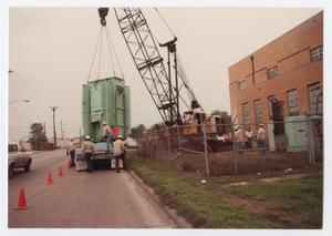 Primary view of object titled '[Crane placing old power plant equipment on truck]'.