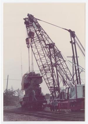 Primary view of object titled '[Diesel generator placed on railroad car by cranes]'.