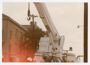 Primary view of object titled '[Public utility worker using a crane on E. Mulberry Street]'.