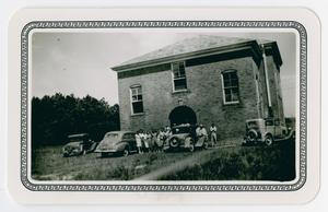 [Photograph of People with Automobiles Outside Brick Building]