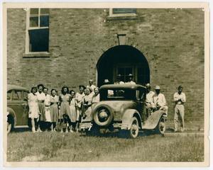 [Photograph of People Beside Automobiles Outside Brick Building]