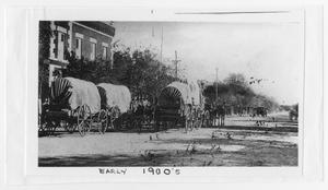 Primary view of object titled '[Photograph of Covered Wagons on Street]'.