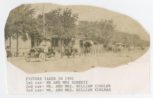 Primary view of object titled '[Photograph of Couples Driving Automobiles Down a Street]'.