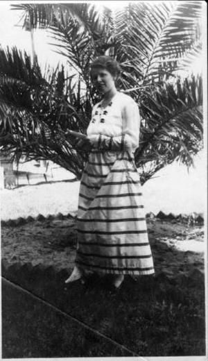 Primary view of object titled '[Photograph of Mrs. McCamely in front of a large shrub in a yard]'.