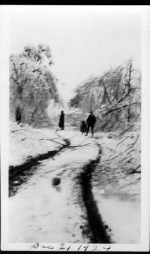 Primary view of object titled '[Tire tracks in the snow and people standing in the distance]'.
