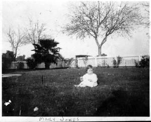 Primary view of object titled '[Photograph of Mary Jones as an infant sitting in the yard of the George house]'.