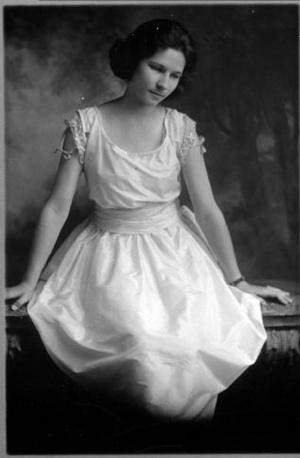 Primary view of object titled '[An unidentified young woman sitting on a bench and wearing a white gown]'.