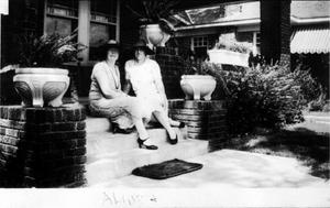 Primary view of object titled '[Aline and an unknown woman sitting on the steps of a brick front porch]'.