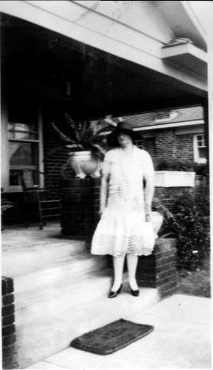 Primary view of object titled '[Aline standing on steps, wearing a white lace dress and a black hat]'.