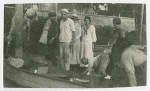 [Photograph of a Group Preparing a Small Canoe]