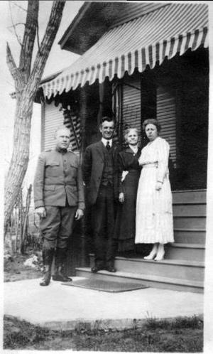 Primary view of object titled '[Mary E. Molly George, Two men, and a woman standing on porch steps]'.