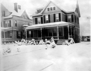 Primary view of object titled '[An unidentified two story house with small bushes covered in snow]'.