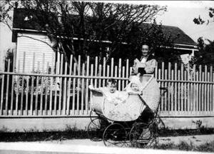 Primary view of object titled '[An older woman standing next to two small children in a carriage]'.