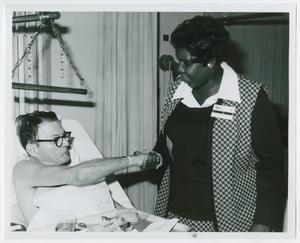 Primary view of object titled '[Barbara Jordan Shakes Hands with a Patient of Houston Veterans Administration Hospital]'.