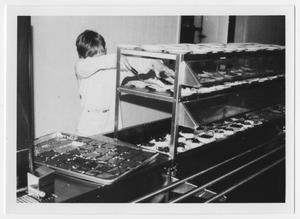 Primary view of object titled '[A Boy Serves Cake in a Dining Line]'.