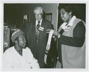 Primary view of object titled '[Barbara Jordan Signs an Autograph of a Patient of Houston Veterans Administration Hospital]'.