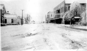 Primary view of object titled '[A snow covered street lined with buildings on both sides]'.