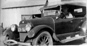 Primary view of object titled '[A man in an automobile, parked in front of a tin shed]'.