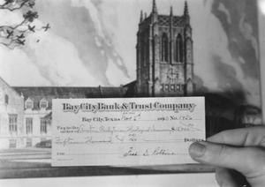 [Donation Check Being Held up to an Artist's Rendering of Shelton Chapel]