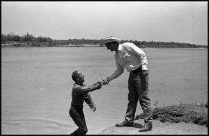[Photograph of a man helping other out of lake.]
