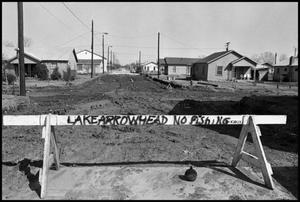 [Blocked torn up road in housing development.]