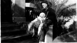 Primary view of object titled '[A man sitting on the edge of a platform holding a gun, with two dogs on his lap]'.