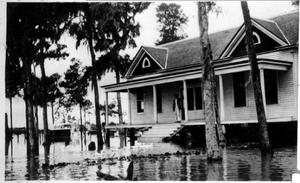 Primary view of object titled '[Photograph of an Unidentified Person Standing on a House Porch During a Flood]'.