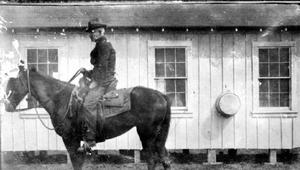 Primary view of object titled '[An older gentlemen on a horse behind the Davis cook's quarters]'.