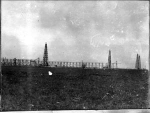 Primary view of object titled '[Photograph of four large oil derricks in a field]'.