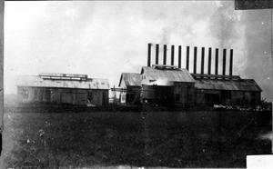 Primary view of object titled '[An industrial factory with twelve smoke stacks protruding from the top]'.