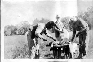 Primary view of object titled '[Three men in a field at Camp George, preparing meat from a hunt]'.