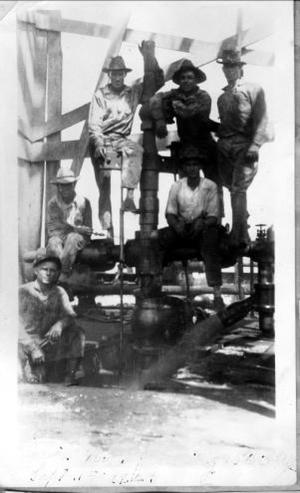 Primary view of object titled '[Photograph of six men sitting on and around oil pipes]'.
