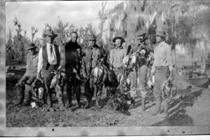 Primary view of object titled '[Photograph of seven men in a row following a hunt]'.