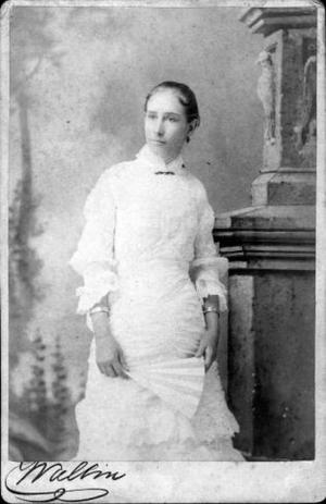 Primary view of object titled '[Woman wearing a white dress and standing by a large column]'.